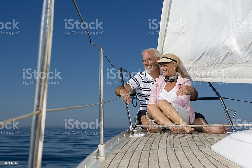 Couple sitting on a sailboat stock photo
