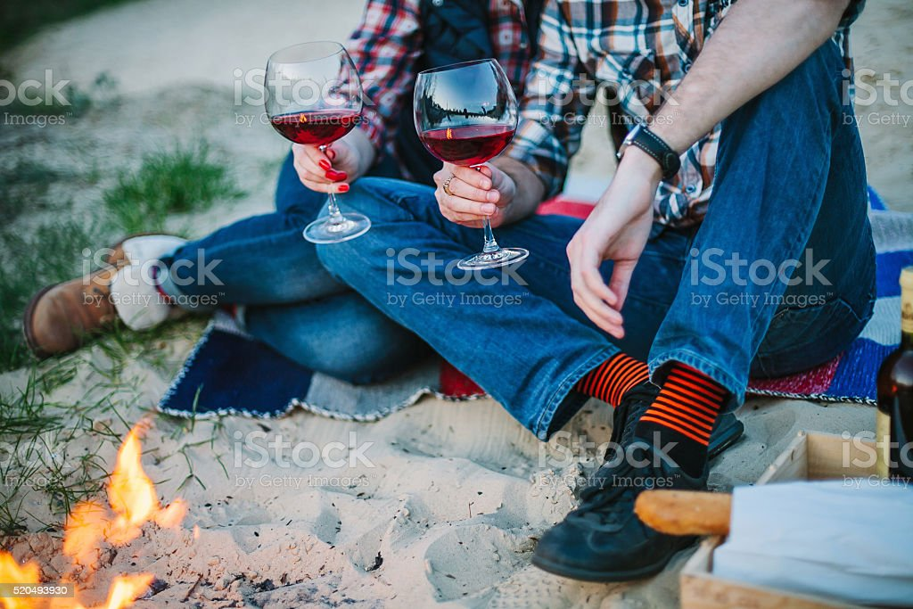 Couple sitting on beach and drinking wine in the evening stock photo