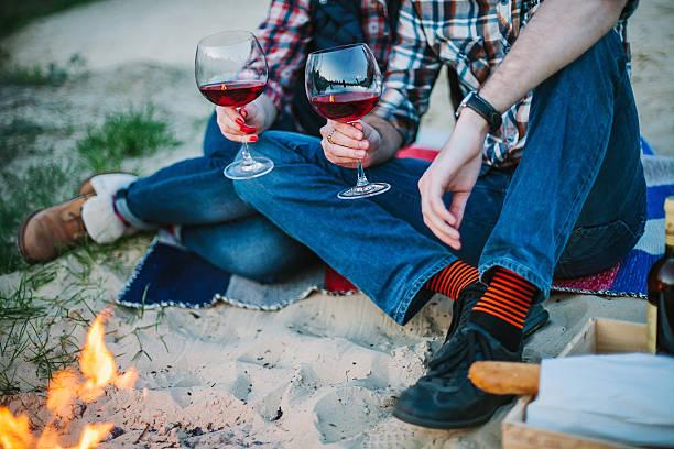 coppia seduto su spiaggia e bere vino alla sera - falò spiaggia foto e immagini stock