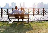 Couple sitting on bench by the sea.