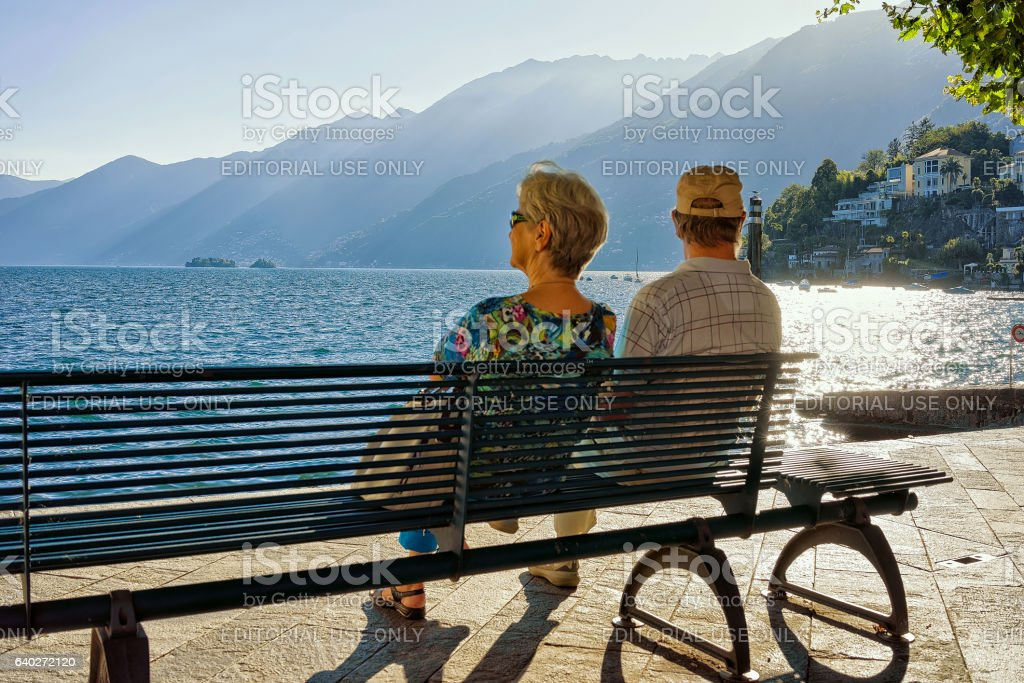 Couple sitting on bench in Ascona resort of Ticino Switzerland stock photo