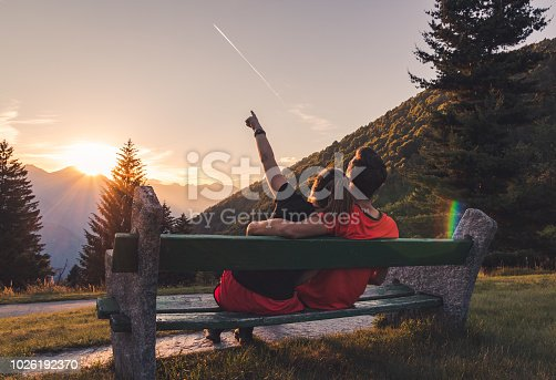 couple in love resting on a bench in the swiss alps dreaming about vacations