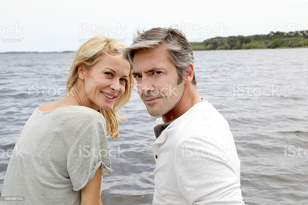 Couple sitting on bridge and looking at camera royalty-free stock photo
