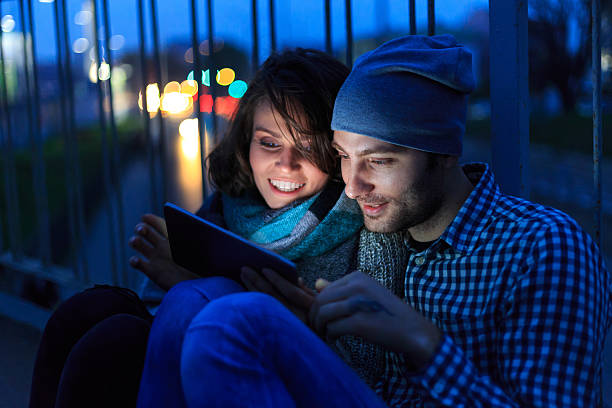 couple sitting on bridge and using digital tablet at night - mobile game stock photos and pictures