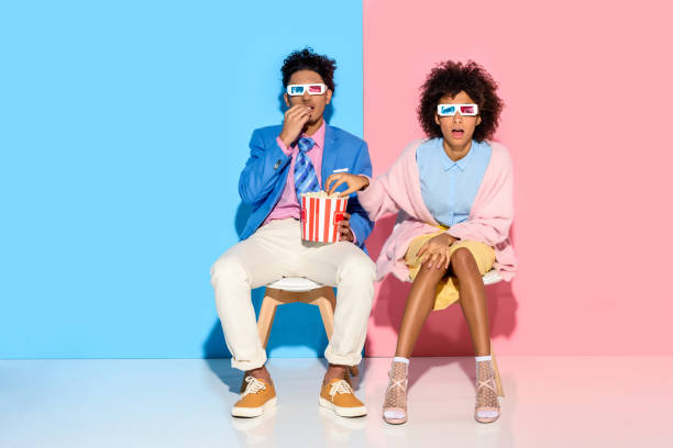 couple sitting on chairs and eating popcorn stock photo