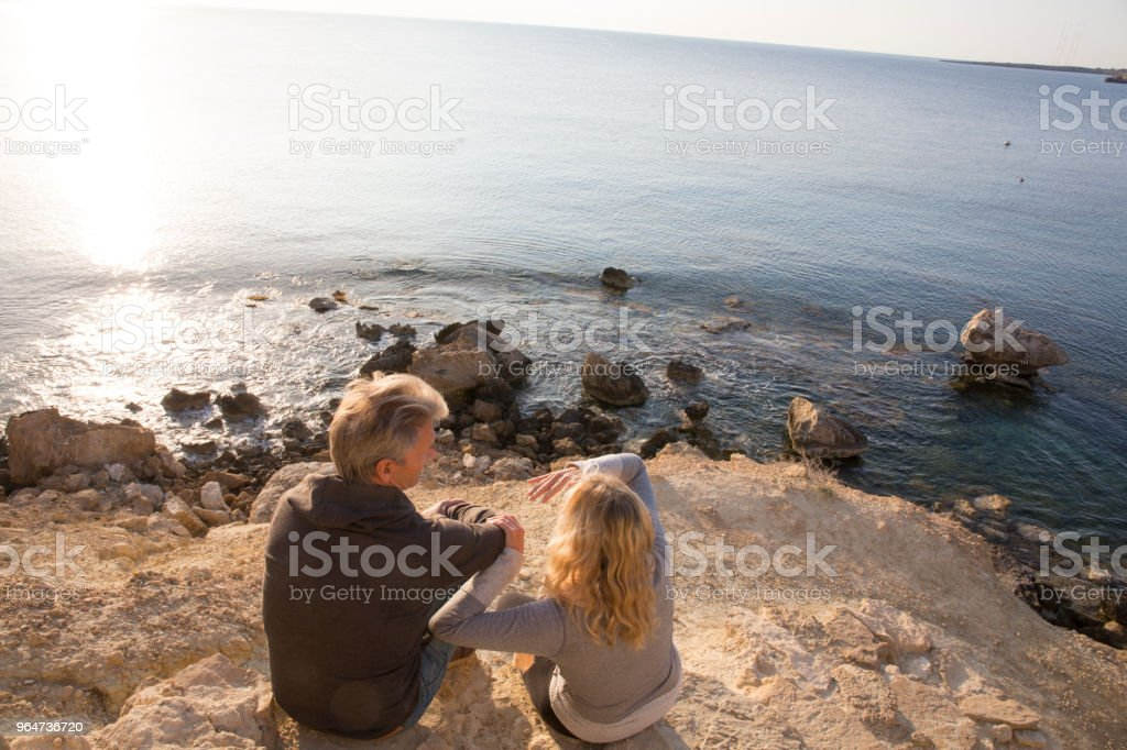 Couple sitting on coastal rocks above sea royalty-free stock photo