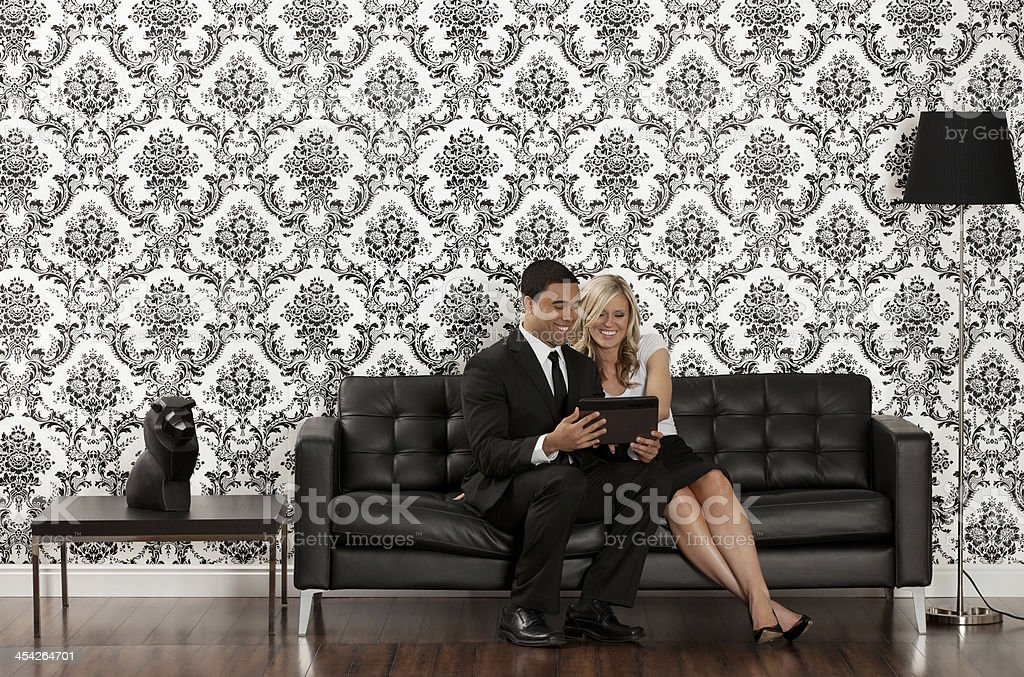 Couple sitting on couch and looking at a tablet royalty-free stock photo