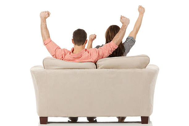 Couple sitting on couch raising hands stock photo