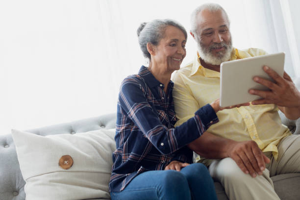 Couple sitting on couch while using a tablet stock photo