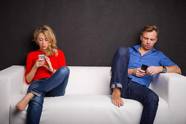Couple sitting on couch with their phones in their hand stock photo