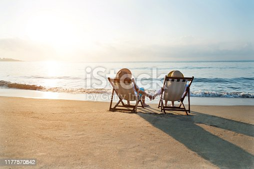 Couple sitting on deck chair at beach.