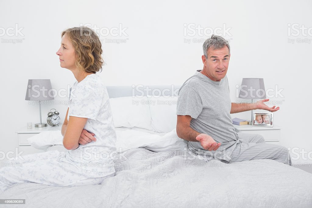 Couple sitting on different sides of bed having a dispute stock photo