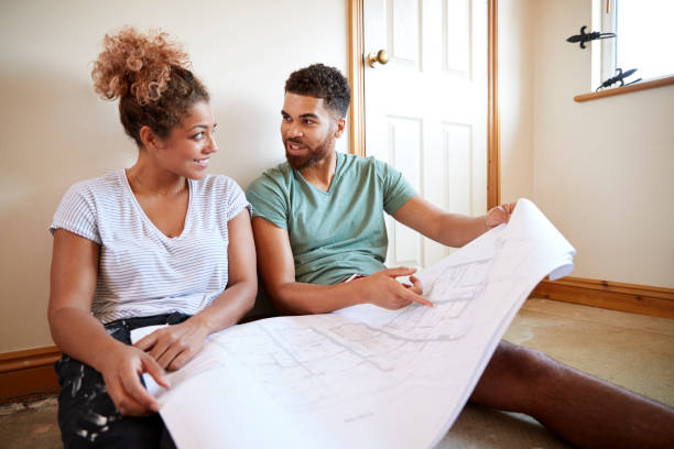 Couple Sitting On Floor Looking At Plans In Empty Room Of New Home Couple Sitting On Floor Looking At Plans In Empty Room Of New Home home improvement stock pictures, royalty-free photos & images