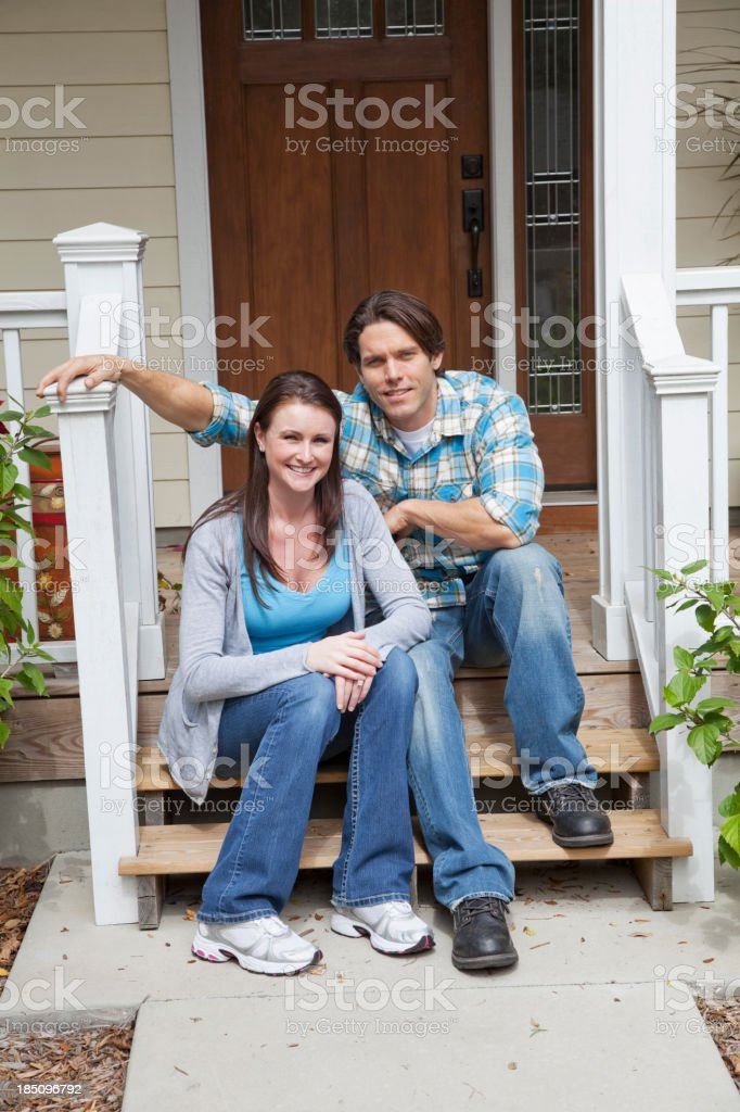 Couple sitting on front steps stock photo
