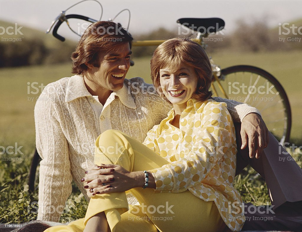 Couple sitting on grass, bicycle in background stock photo