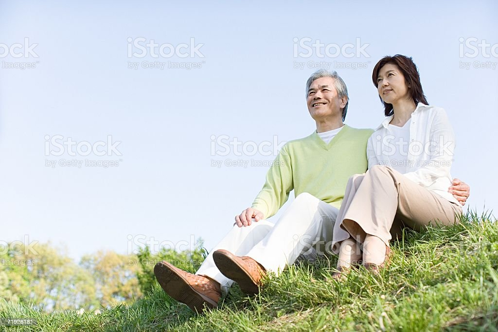 Couple sitting on grass stock photo