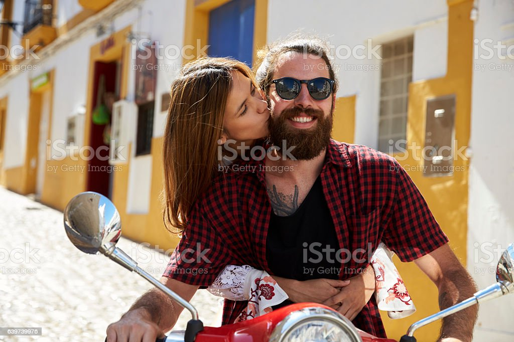 Couple sitting on motor scooter, she kisses him on the cheek stock photo