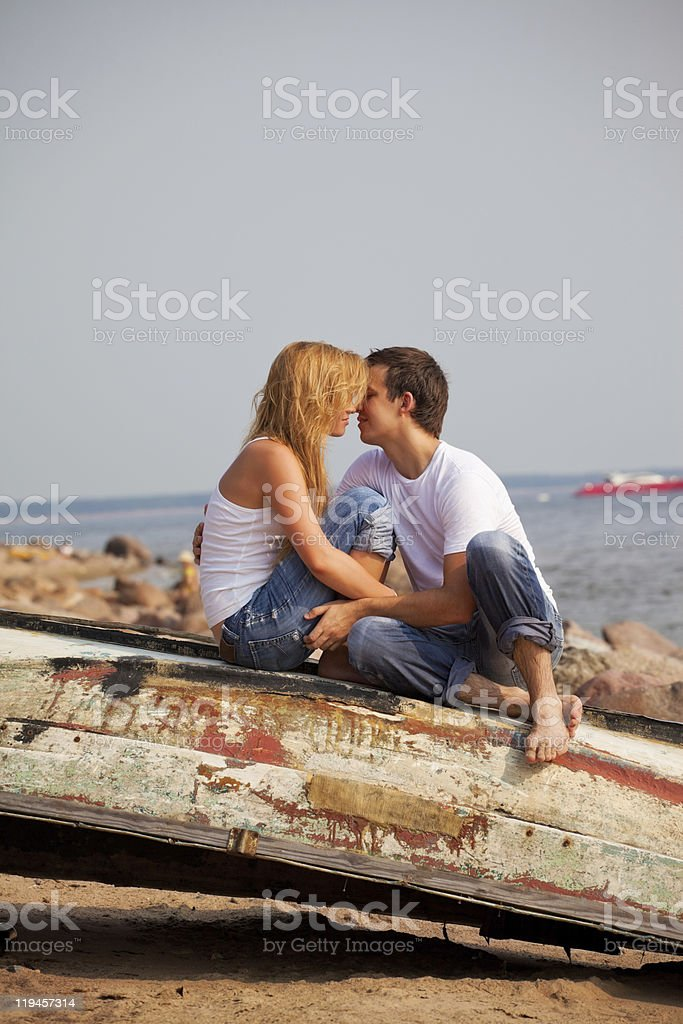 couple sitting on old boat and kiss royalty-free stock photo