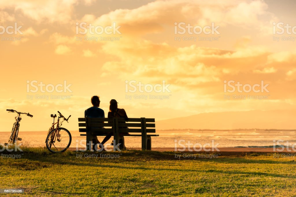 Couple sitting on park bench watching the sunset. stock photo