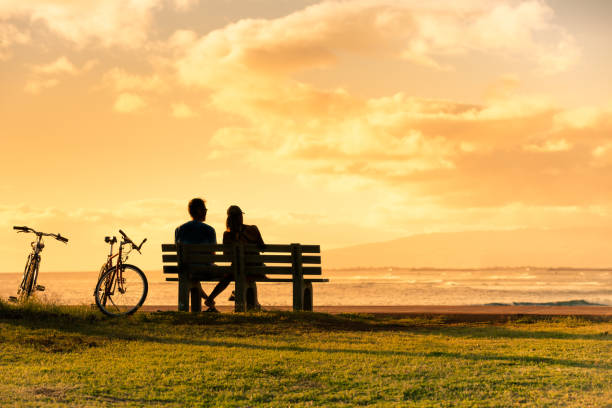 couple assis sur un banc de parc au coucher du soleil. - banc photos et images de collection