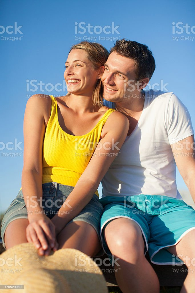couple sitting on pier together royalty-free stock photo