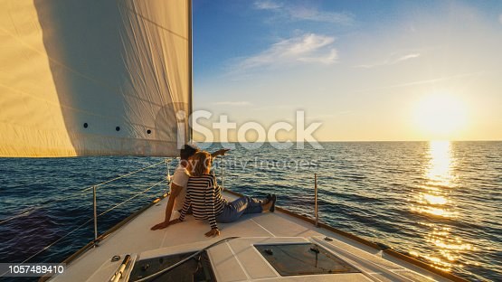 Couple sitting on prow of boat, man pointing his hand, Croatia