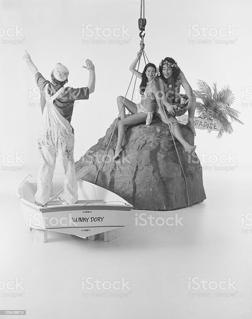 Couple sitting on rock another standing in boat royalty-free stock photo