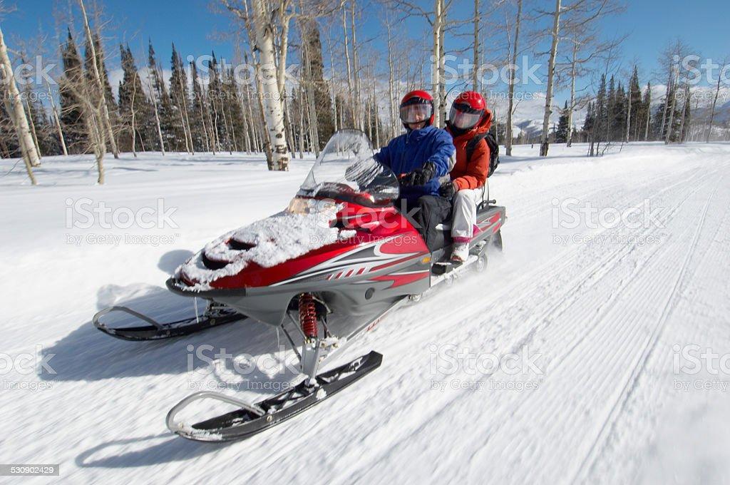 Couple Sitting on Snowmobile stock photo