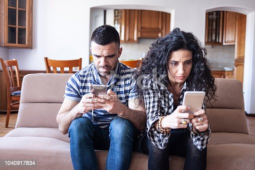 Couple having relationship problems, sitting on sofa at home.