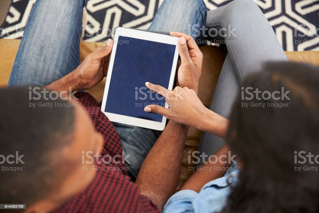 Couple Sitting On Sofa At Home Looking At Digital Tablet stock photo