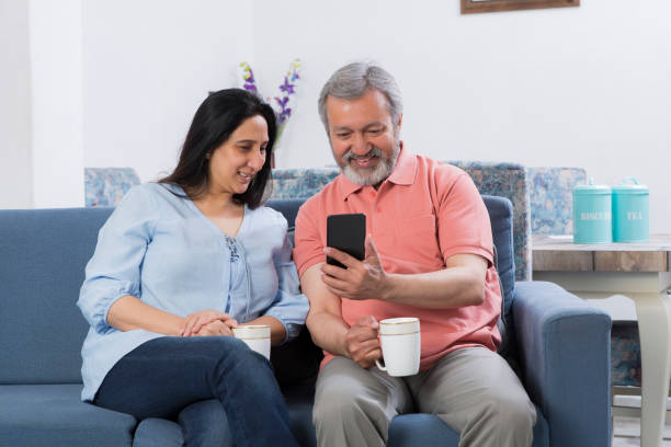 pareja sentada en el sofá en la sala de estar foto de archivo - happy couple sharing a cup of coffee fotografías e imágenes de stock
