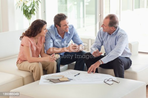 istock Couple sitting on sofa talking to financial advisor 135385049