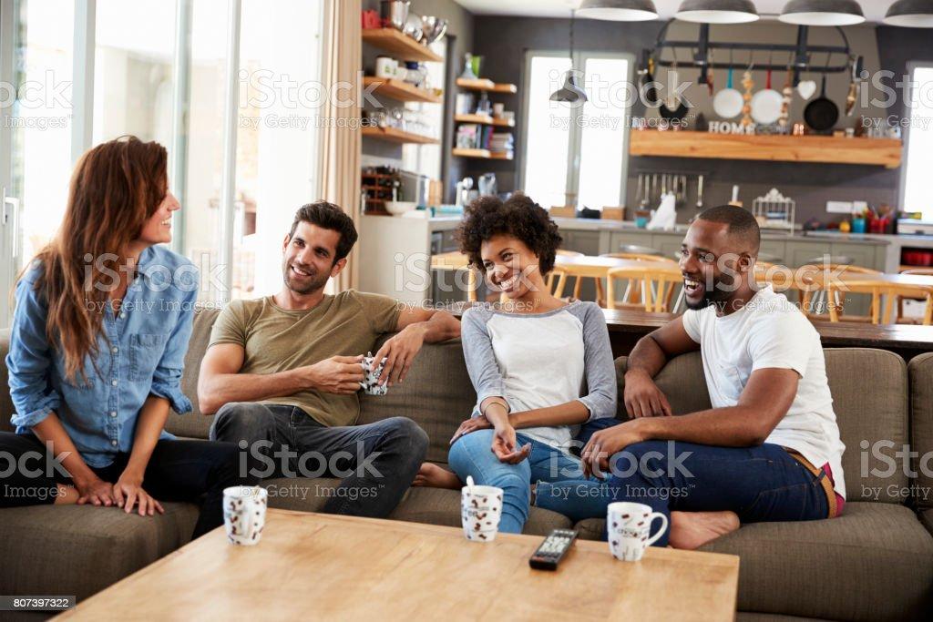 Pareja sentada en el sofá con los amigos en casa hablando - foto de stock