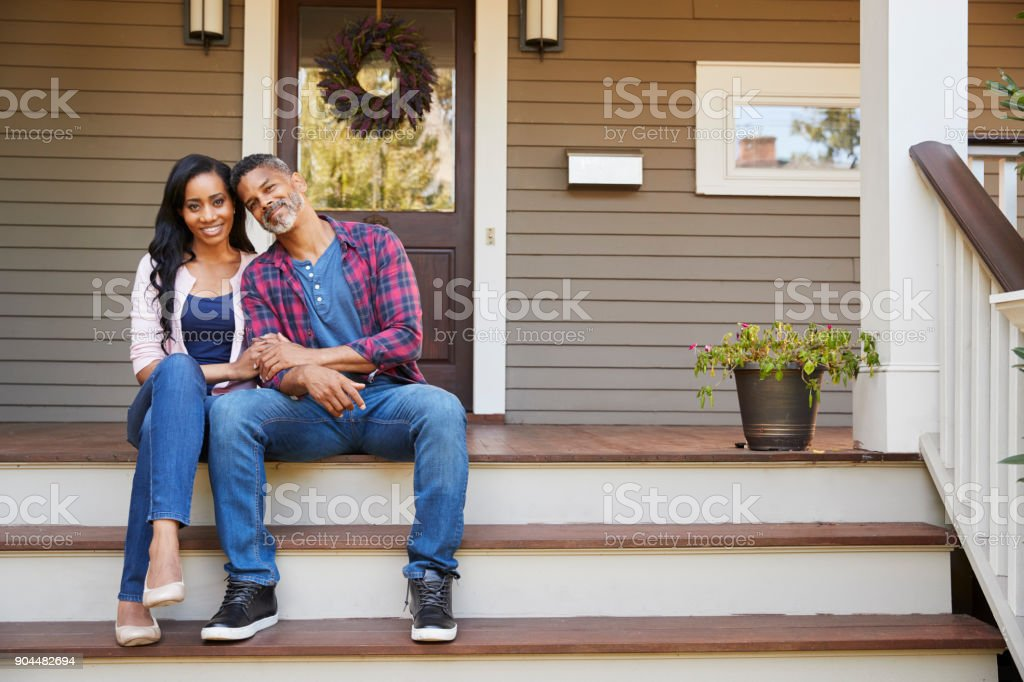 Couple Sitting On Steps Leading Up To Porch Of Home stock photo