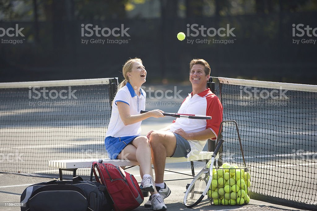 Couple Sitting on Tennis Court stock photo