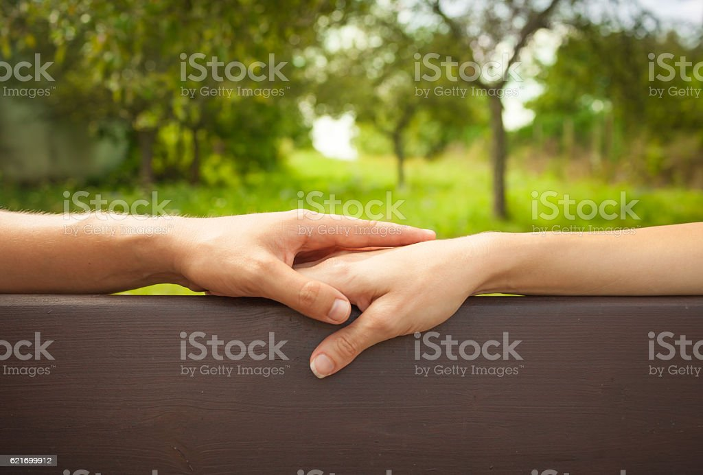 Couple sitting on the bench holding hands stock photo