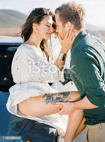 628541610istockphoto Couple sitting on the car. 1160368443