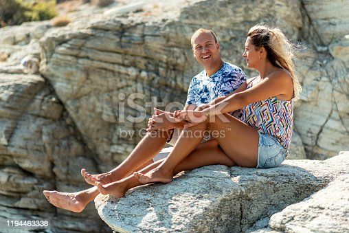 couple sitting on the rock watching the view