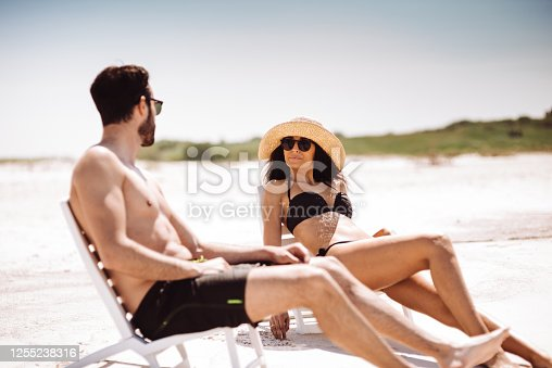 couple sitting on the sunbed at the seaside
