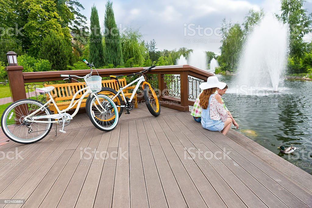 Couple sitting on the wooden deck after biking and feeding stock photo