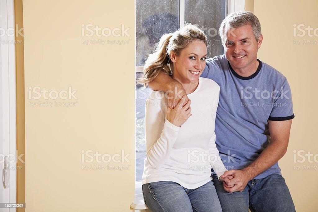 Couple sitting on window sill stock photo