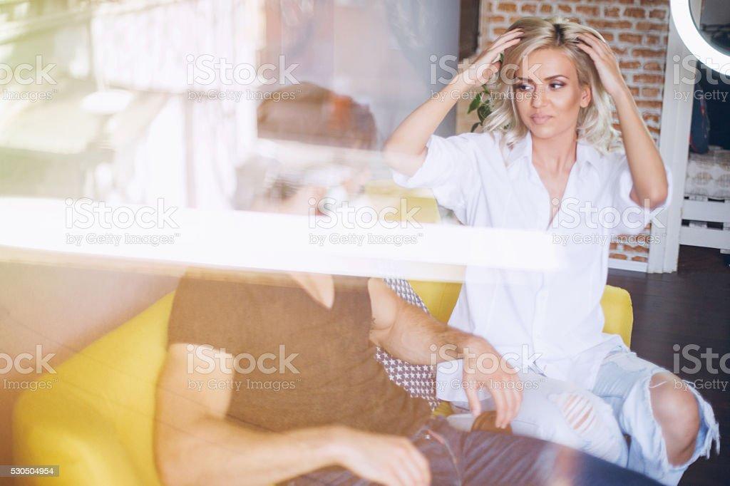 Couple sitting on yellow sofa stock photo