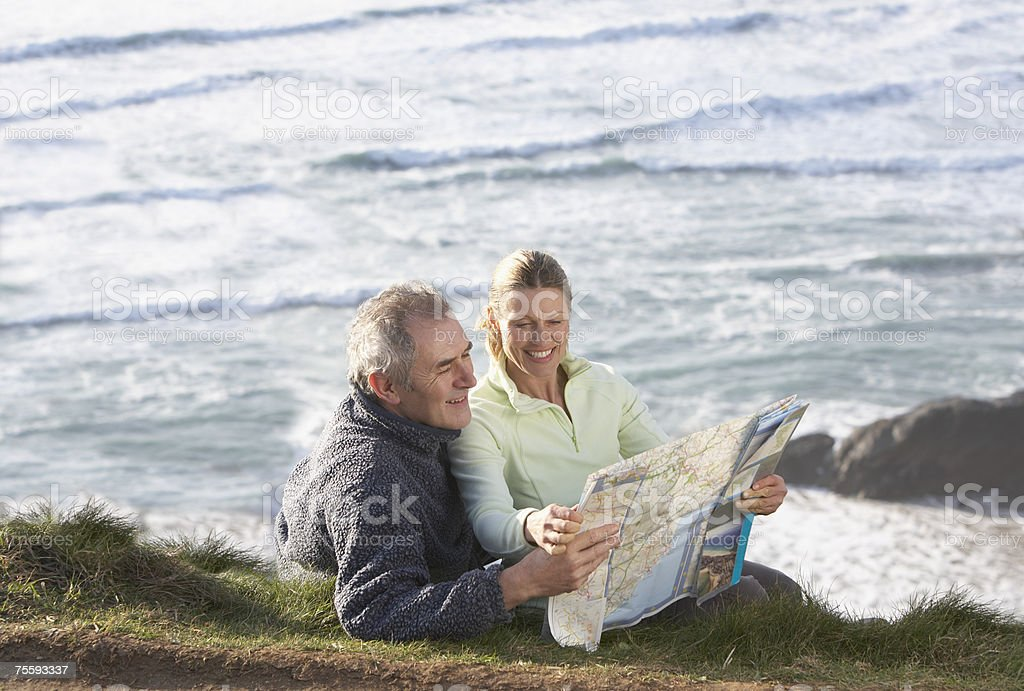 Couple sitting outdoors reading a map royalty-free stock photo