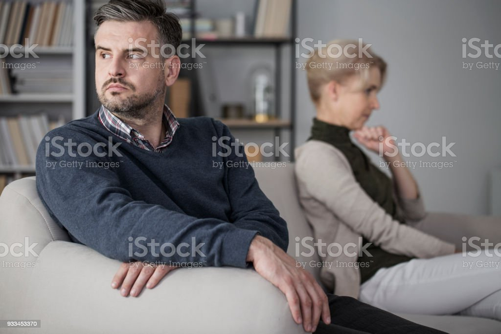 Couple sitting separately stock photo