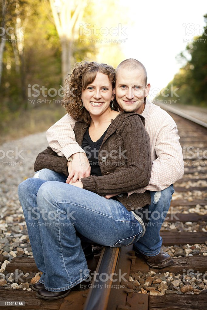Couple Sitting Together Outside On Railroad Tracks royalty-free stock photo