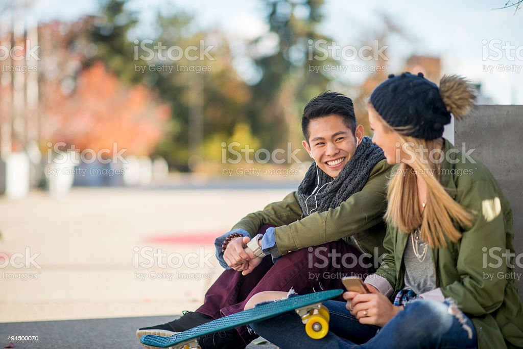Couple Sitting Together Outside A couple is sitting together outside after class with a skateboard before class. 2015 Stock Photo