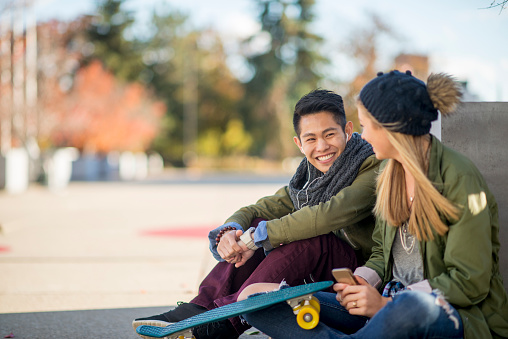 Couple Sitting Together Outside Stock Photo - Download Image Now