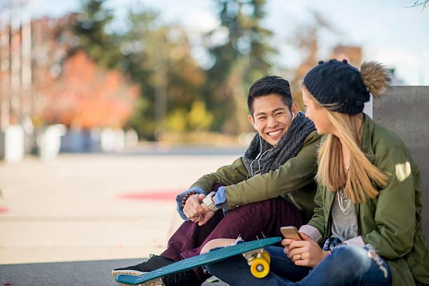 coppia seduta insieme all'esterno - compagni scuola foto e immagini stock
