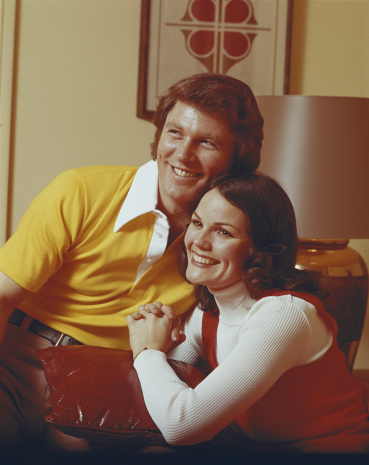Couple sitting with cushion, smiling