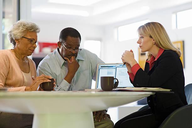coppia seduto con il consulente finanziario a casa - pensionati lavoratori foto e immagini stock